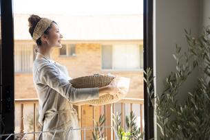 洗濯物の入ったかごを持っている女性の写真素材 [FYI01707380]