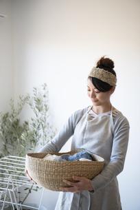 洗濯物の入ったかごを持っている女性の写真素材 [FYI01707393]