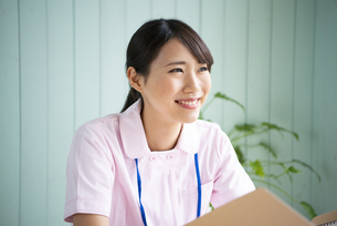 制服姿でファイルを持って笑っている女性の写真素材 [FYI01707407]