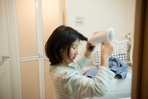 ドライヤーで髪を乾かしている女の子の写真素材 [FYI01707411]
