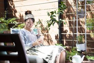 庭でくつろぎながらスマホを見ている女性の写真素材 [FYI01707412]