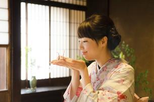 手のひらに折り鶴を乗せた着物姿の女性の写真素材 [FYI01707425]