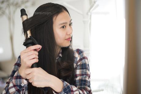 髪の毛を巻いている女性の写真素材 [FYI01707441]