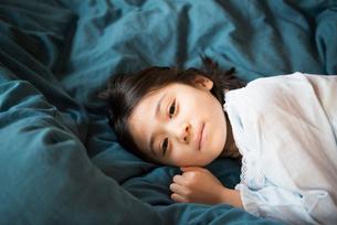 ベッドに寝転がっている女の子の写真素材 [FYI01707445]