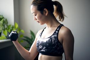 ジムでダンベルを使って筋トレをしている女性の写真素材 [FYI01707449]