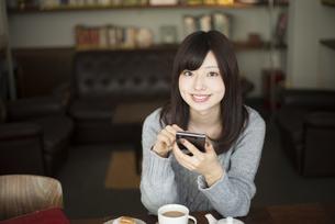 カフェでスマホを触っている女性の写真素材 [FYI01707457]