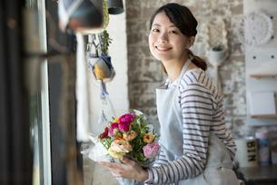 花束を持っている笑顔の店員の女性の写真素材 [FYI01707467]