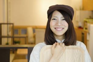 制服を着てカフェで働く女性の写真素材 [FYI01707473]