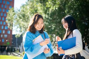 スマホを見て笑っている大学生の写真素材 [FYI01707498]