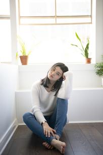 フローリングの床に座っている女性の写真素材 [FYI01707501]