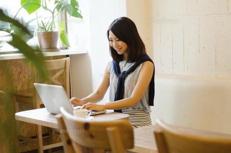 カフェでノートパソコンで仕事をしている女性の手元の写真素材 [FYI01707505]