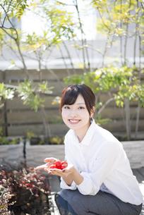 屋上でトマトを持っている女性の写真素材 [FYI01707511]