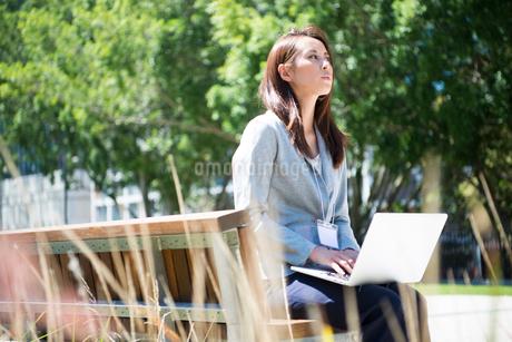 パソコンを持ってベンチに座っている女性の写真素材 [FYI01707526]