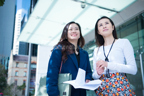 オフィス街で遠くを見ている女性2人の写真素材 [FYI01707531]