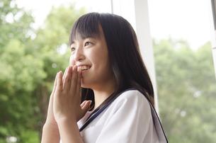 手を合わせて笑う女子高生の写真素材 [FYI01707552]
