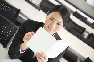 スケジュール帳を見ているスーツ姿の女性の写真素材 [FYI01707588]
