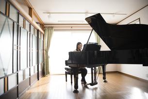 室内でグランドピアノを弾いている女性の写真素材 [FYI01707598]