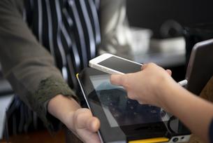 お店でスマホを使って電子決済をしている女性の写真素材 [FYI01707609]