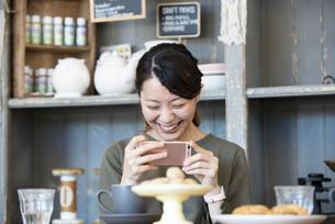 カフェでスマホを使ってスイーツの写真を撮っている女性の写真素材 [FYI01707611]