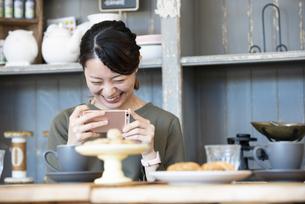カフェでスマホを使ってスイーツの写真を撮っている女性の写真素材 [FYI01707646]