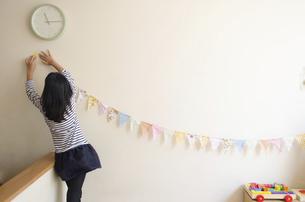 家の飾りつけをしている女の子の写真素材 [FYI01707656]