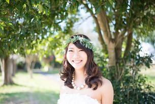 森の中で笑っているウェディングドレス姿の女性の写真素材 [FYI01707658]