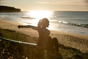 ビーチに座っているウェットスーツ姿の女性の写真素材 [FYI01707667]