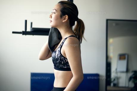 ジムで汗を拭きながら休憩をしている女性の写真素材 [FYI01707670]