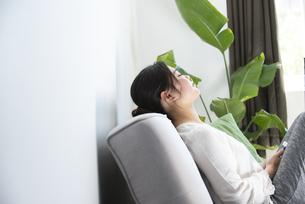 ソファに座って目を閉じている女性の写真素材 [FYI01707682]