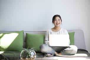 ソファに座ってパソコンを操作しながら笑っている女性の写真素材 [FYI01707686]