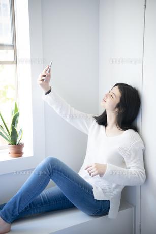 窓辺に座ってスマホで自撮りをしている女性の写真素材 [FYI01707691]