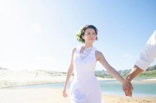 ビーチで手をつないでいるドレス姿の女性の写真素材 [FYI01707706]
