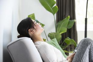 ソファに座って目を閉じている女性の写真素材 [FYI01707719]