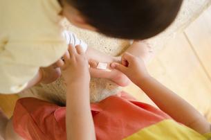 小さな子に絆創膏を貼っている女の子の手の写真素材 [FYI01707720]