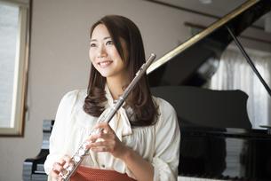ピアノの前でフルートを持っている女性の写真素材 [FYI01707721]