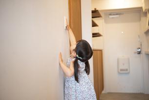 照明のスイッチを触っている女の子の写真素材 [FYI01707743]