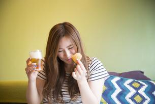 部屋でポテトチップを食べている女性の写真素材 [FYI01707744]