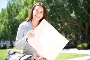 ファイルを広げて笑っている女性の写真素材 [FYI01707753]