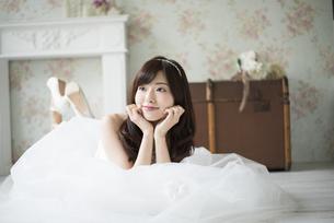 ウェディングドレスを着て寝そべっている女性の写真素材 [FYI01707755]