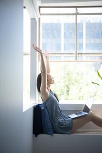 パソコンを足に乗せてストレッチをしている女性の写真素材 [FYI01707759]