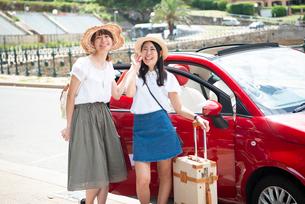 赤い車の前に立って笑っている女性2人の写真素材 [FYI01707800]