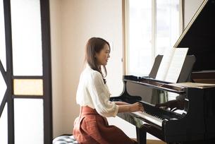 室内でグランドピアノを弾いている女性の写真素材 [FYI01707802]