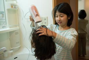ドライヤーで髪を乾かしている姉妹の写真素材 [FYI01707815]