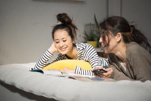 ベッドの上で話している女性2人の写真素材 [FYI01707821]