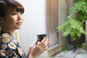 お茶の入った湯のみを持つ着物姿の女性の写真素材 [FYI01707831]