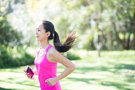 森の中をスマホを持ちながら走っている女性の写真素材 [FYI01707845]