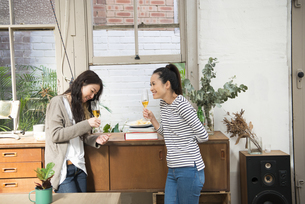 家で飲みながらおしゃべりをしている女性2人の写真素材 [FYI01707866]