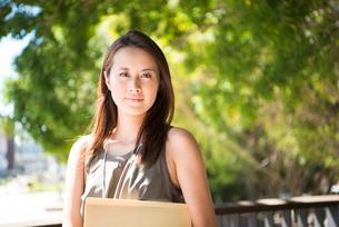 外でこちらを見ている働く女性の写真素材 [FYI01707884]