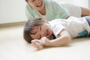 床に転がって笑っている男の子の写真素材 [FYI01707913]