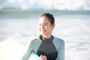 サーフボードを抱えて笑っているウェットスーツ姿の女性の写真素材 [FYI01707933]